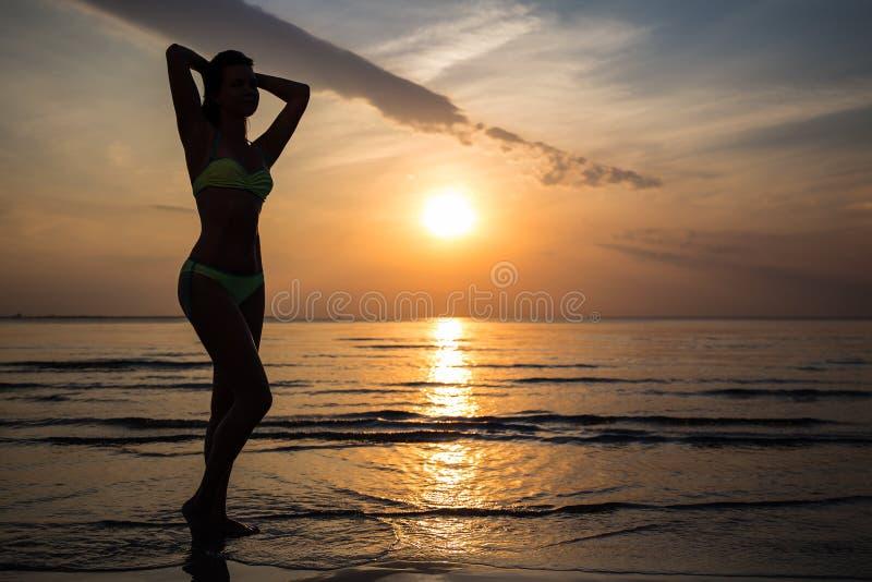 妇女剪影摆在海滩的比基尼泳装的在日落 免版税库存图片