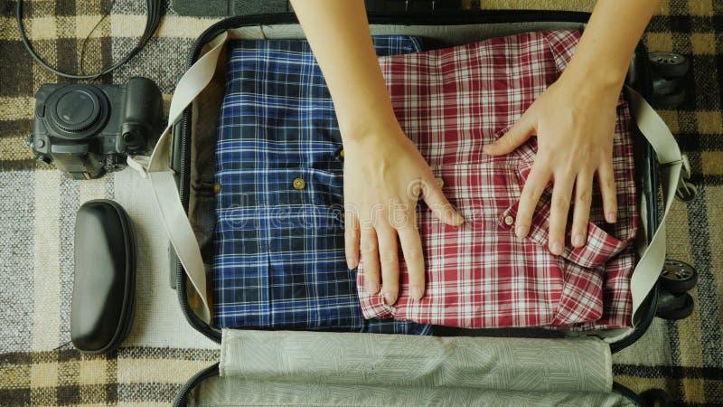 妇女包装一个手提箱 它为旅行汇集事 库存照片