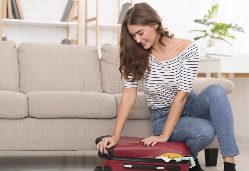 妇女包装为假期,设法关闭手提箱 库存图片