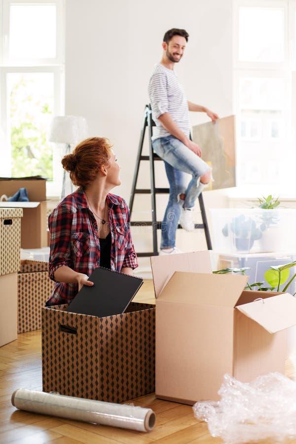妇女包装材料到箱子里,当搬出与丈夫向时 库存照片