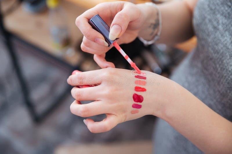 妇女化妆师测试嘴唇的手在手边上光 库存照片