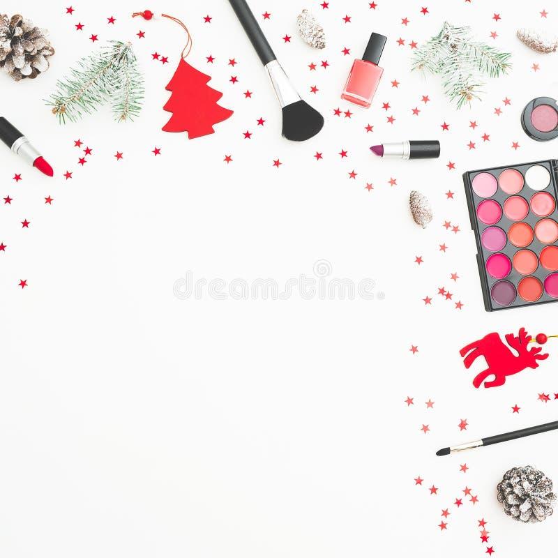 妇女化妆用品、辅助部件和圣诞节装饰,在白色背景的五彩纸屑 平的位置,顶视图 免版税库存图片