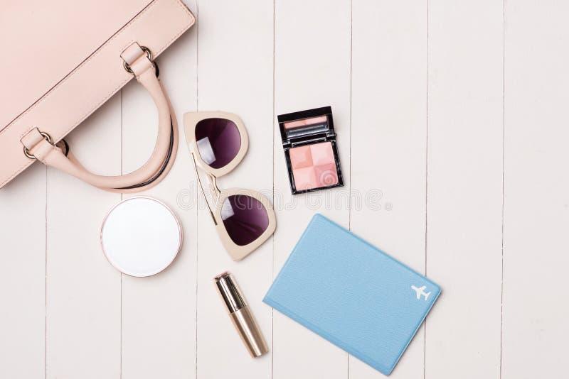 妇女化妆用品和时尚项目在桌上与照相机和passp 免版税库存图片