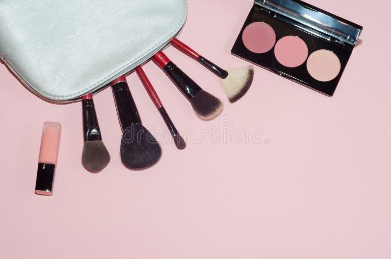 妇女化妆袋子,在桃红色背景组成美容品 构成刷子、桃红色唇膏和胭脂调色板 装饰cosme 库存图片
