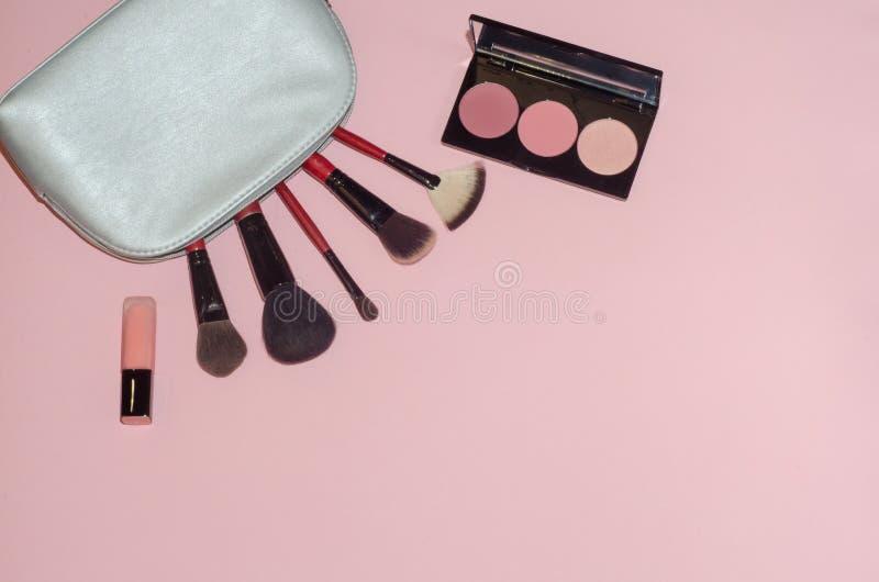 妇女化妆袋子,在桃红色背景组成美容品 构成刷子、桃红色唇膏和胭脂调色板 装饰cosme 免版税库存图片