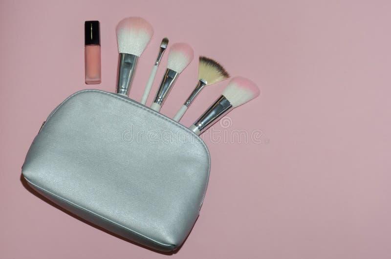 妇女化妆袋子,在桃红色背景组成美容品 构成刷子和桃红色唇膏 顶视图, flatlay 装饰co 免版税图库摄影