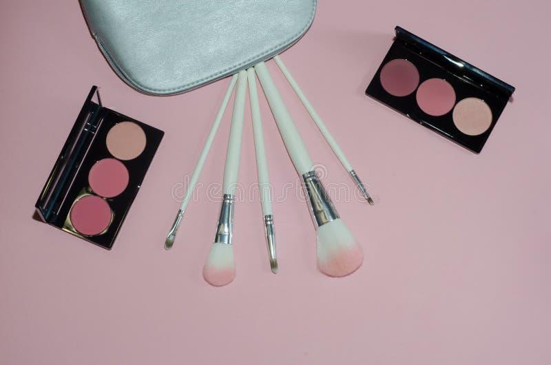 妇女化妆袋子,在桃红色背景组成美容品 构成刷子和胭脂调色板 装饰的化妆用品 顶视图, 库存图片