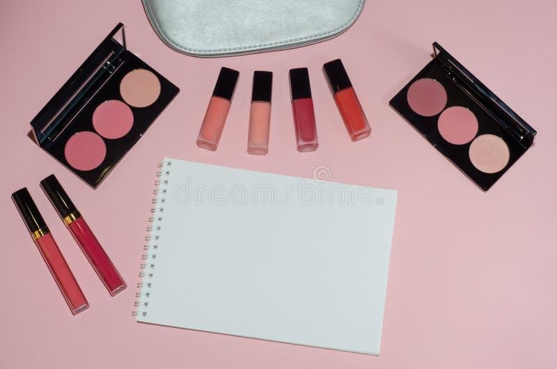 妇女化妆袋子,在桃红色背景,笔记本组成美容品 红色和桃红色唇膏 构成刷子和胭脂调色板 库存照片