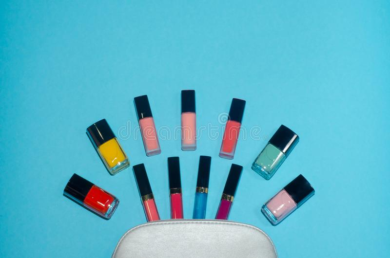 妇女化妆袋子,在蓝色背景组成美容品 红色,桃红色,洋红色和蓝色唇膏 套红色,桃红色,绿色和 库存图片