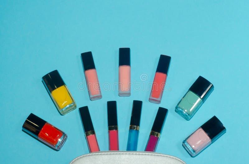 妇女化妆袋子,在蓝色背景组成美容品 红色,桃红色,洋红色和蓝色唇膏 套红色,桃红色,绿色和 免版税库存图片
