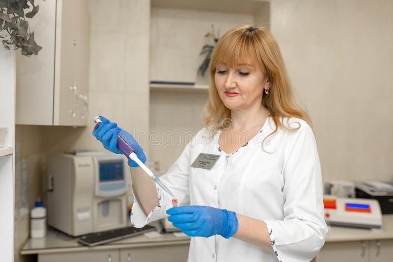 妇女化验员作为从试管的血样 免版税库存图片