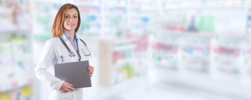 妇女医生在被弄脏的药房int的片剂或膝上型计算机身分 免版税库存图片