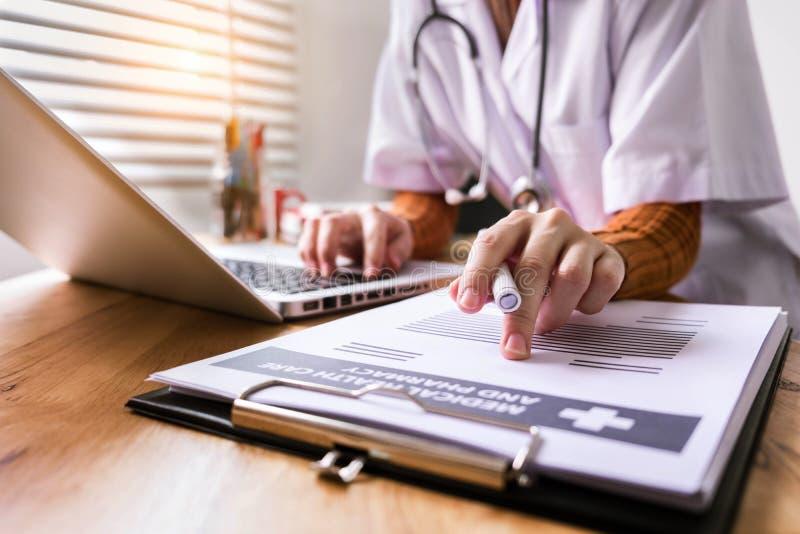 妇女医生坐在办公室写耐心报告 免版税图库摄影