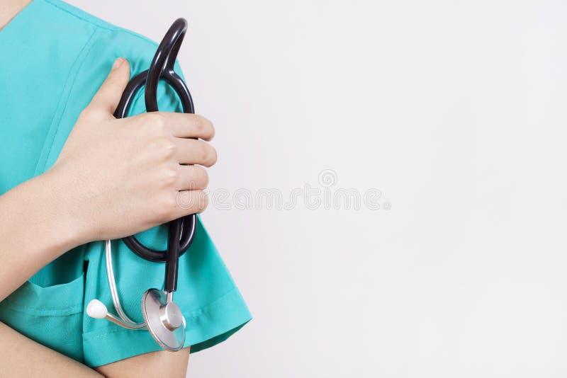 妇女医生手在灰色背景的藏品听诊器 免版税库存照片