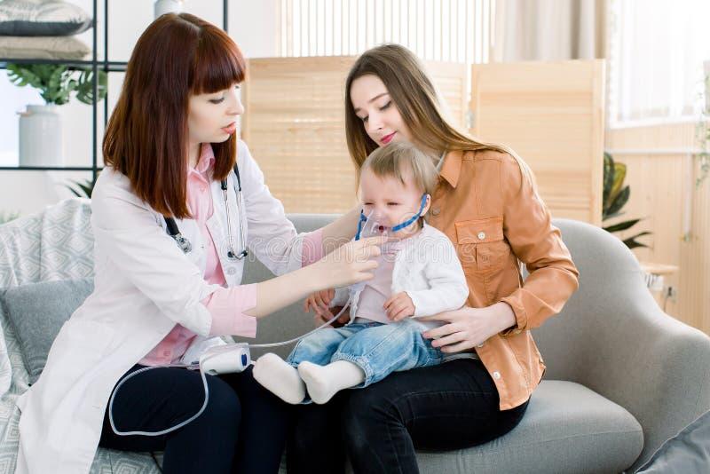 妇女医生拿着一点女婴的一台面具蒸气吸入器 哮喘的治疗 呼吸通过蒸汽雾化器 库存照片