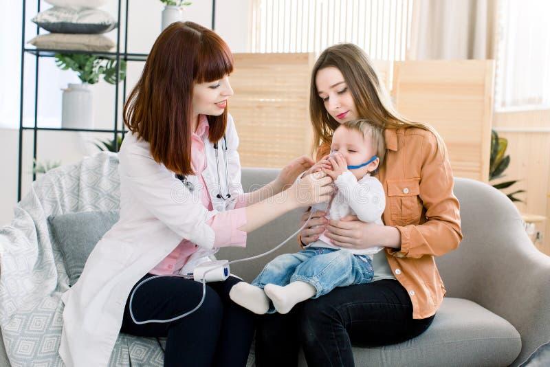 妇女医生拿着一点女婴的一台面具蒸气吸入器 哮喘的治疗 呼吸通过蒸汽雾化器 免版税库存图片