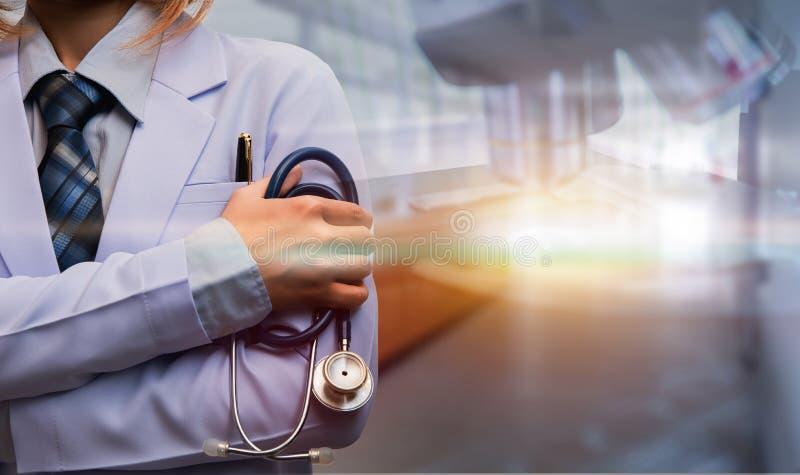 妇女医生横渡的胳膊和举行听诊器 免版税库存图片