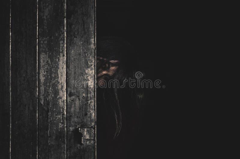 妇女半面孔behide在abandonat房子万圣节概念的门 免版税库存图片