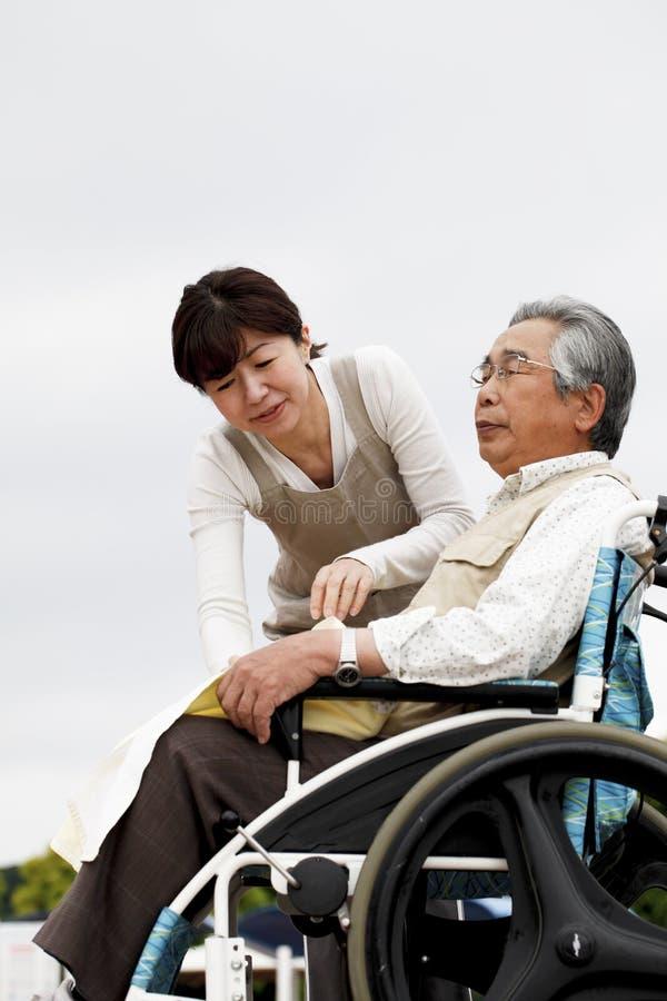 妇女协助了轮椅 免版税库存图片