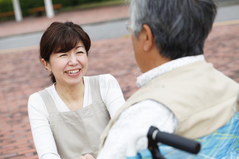 妇女协助了轮椅 库存图片