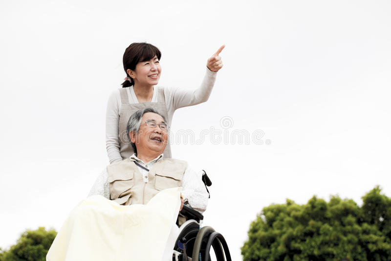 妇女协助了轮椅 图库摄影