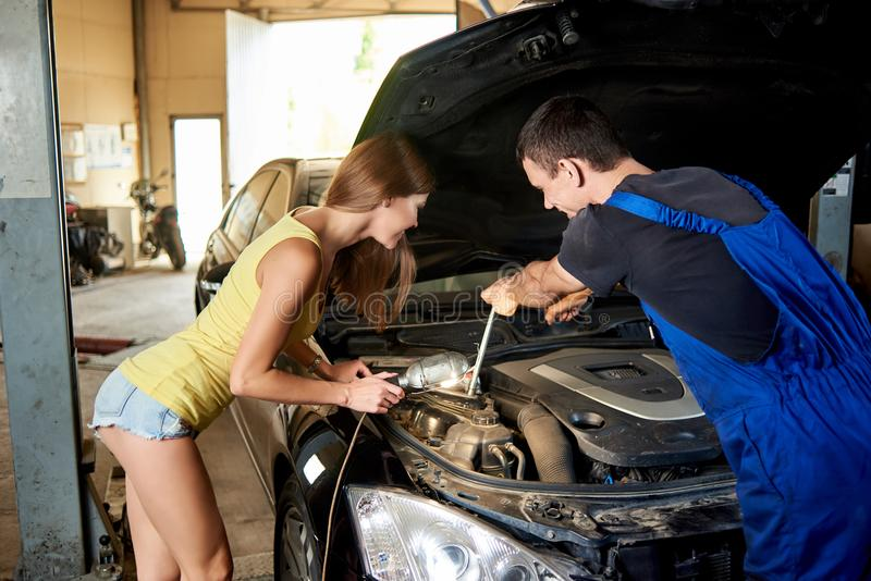妇女协助修理的汽车一位技工 库存图片