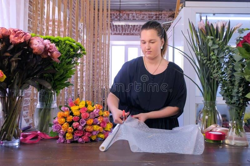 妇女卖花人在植物的商店工作裁减纸板料包装花花束 图库摄影