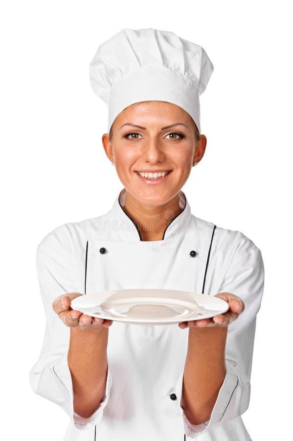 妇女厨师或主厨服务空的牌照的和微笑愉快 库存照片