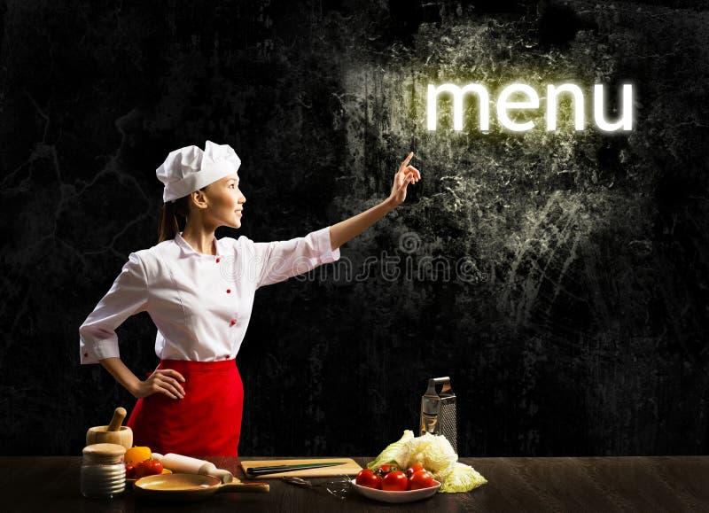妇女厨师接触发光的词菜单 库存图片