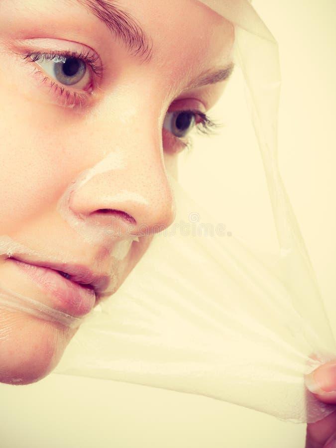 妇女去除面部剥落面具 免版税库存图片