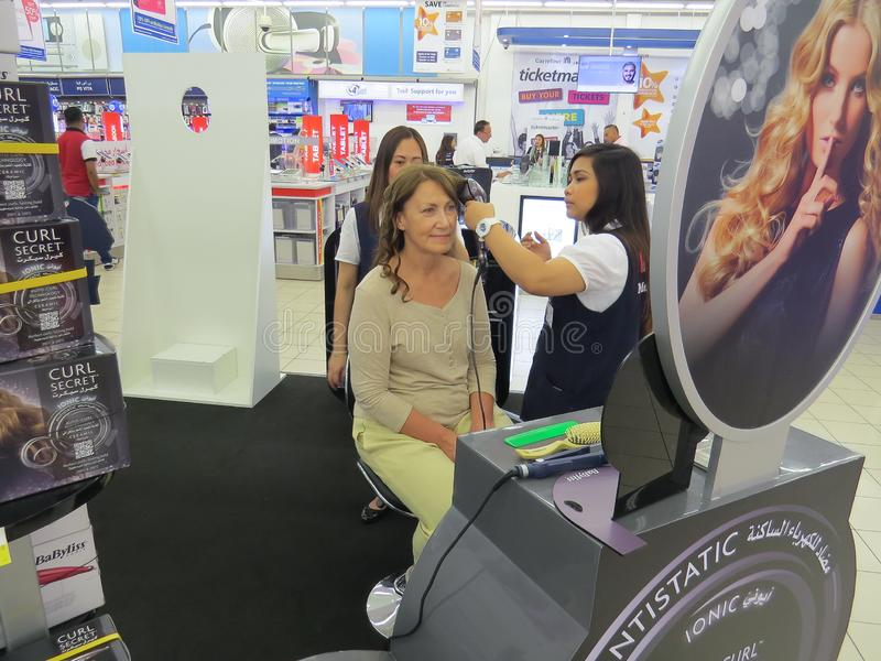 妇女参加一场广告战 女孩卖主在迪拜购物中心做她的与头发styler的卷毛 库存照片