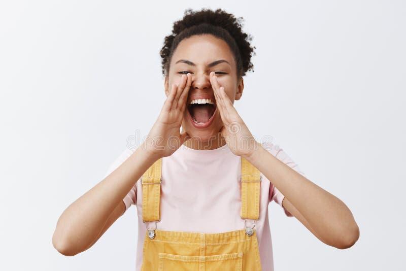 妇女叫喊给朋友大声转过来并且看见她 黄色总体的快乐的无忧无虑的非裔美国人的女朋友 库存图片