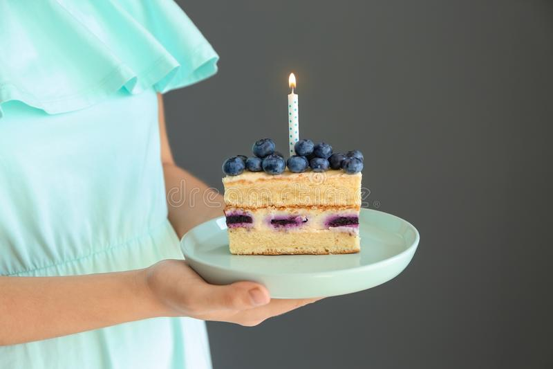 妇女可口生日蛋糕藏品片断与燃烧的蜡烛的在灰色背景 库存图片