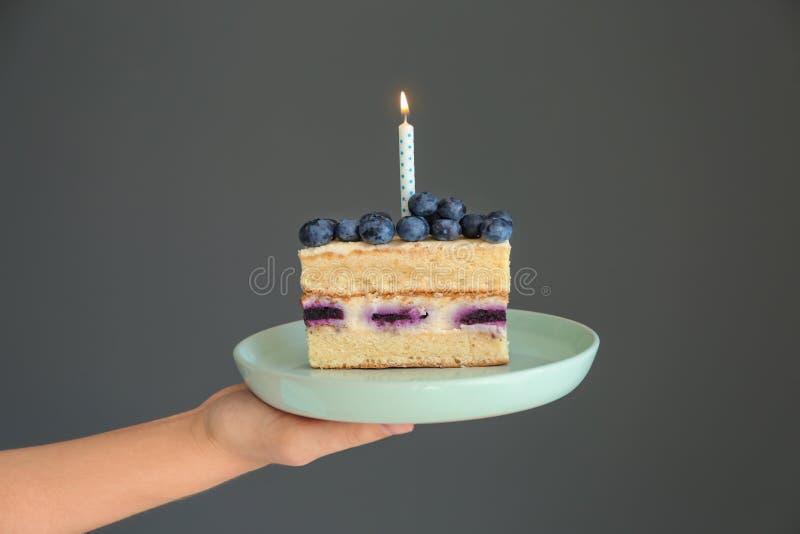 妇女可口生日蛋糕藏品片断与燃烧的蜡烛的在灰色背景 免版税库存图片