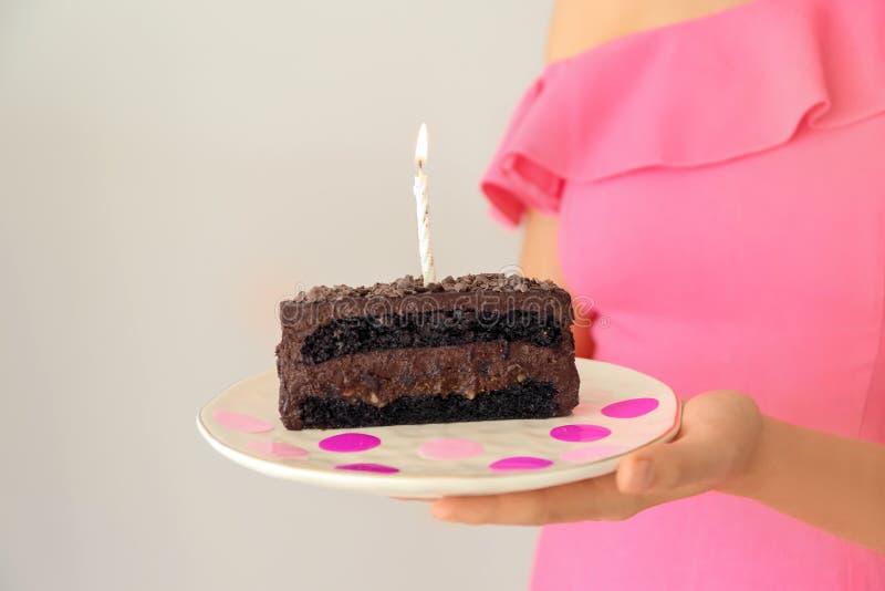妇女可口生日蛋糕藏品片断与燃烧的蜡烛的在轻的背景 库存图片