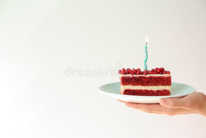 妇女可口生日蛋糕藏品片断与燃烧的蜡烛的在轻的背景 免版税图库摄影