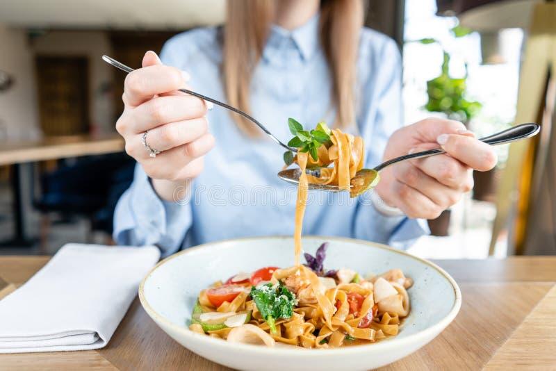 妇女吃意大利面团用海鲜和西红柿酱 面团Gamberini 特写镜头tagliatelle在一把叉子附近包缠它与 免版税库存图片