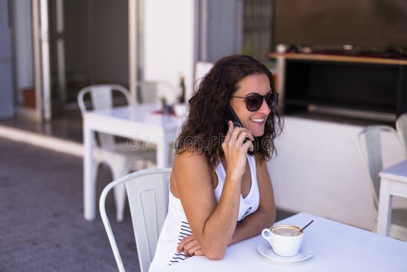 妇女吃早餐在大阳台,谈话在她手机和微笑 早晨、白天和技术 免版税库存照片