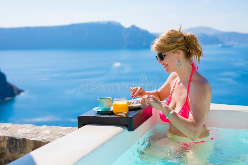 妇女吃早餐,当放松在室外浴缸时 免版税库存图片
