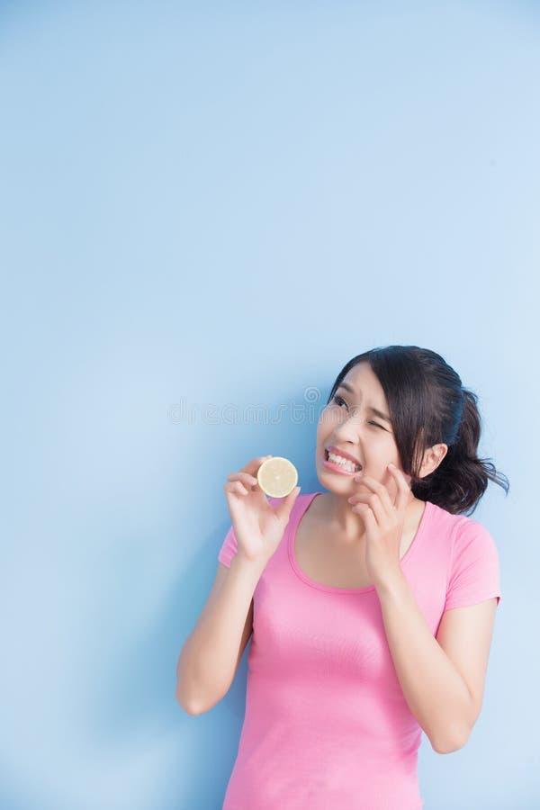 妇女吃酸柠檬的感受 图库摄影