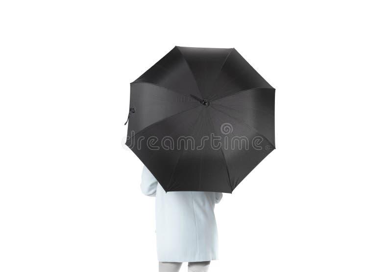 妇女向后站立与黑空白的伞被打开的大模型 库存图片