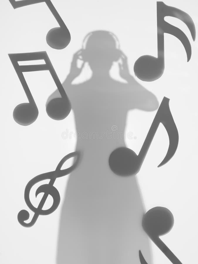 妇女听到音乐的,剪影 免版税库存照片