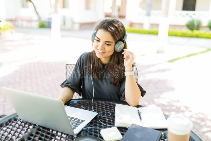 妇女听的音乐,当在网上与膝上型计算机一起使用在庭院里时 免版税库存图片