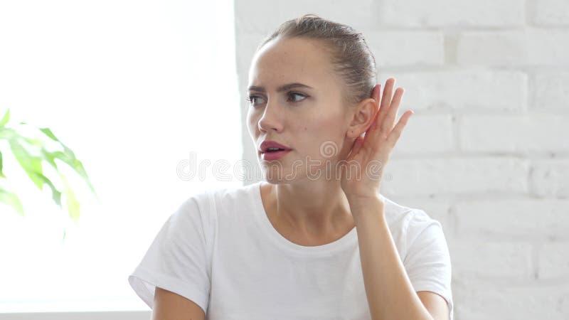 妇女听认真,在耳朵画象的手 免版税库存照片