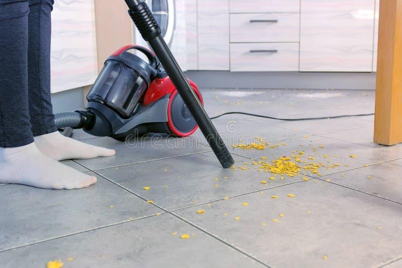 妇女吸尘与灰色瓦片的厨房地板,不用刷子,吸尘器仅管子  特写镜头腿 库存图片