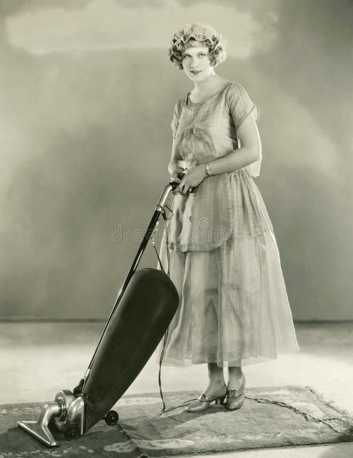 妇女吸尘的地毯 免版税库存图片