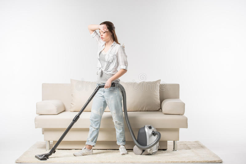 妇女吸尘的地毯 库存照片
