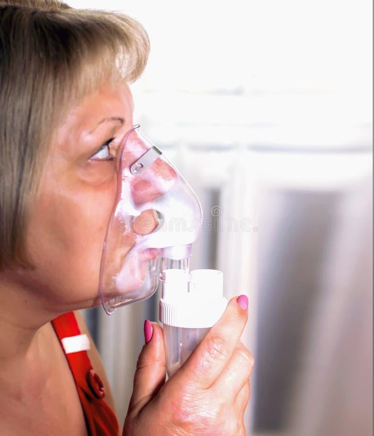 妇女呼吸与吸入器、寒冷的治疗和咳嗽 免版税图库摄影