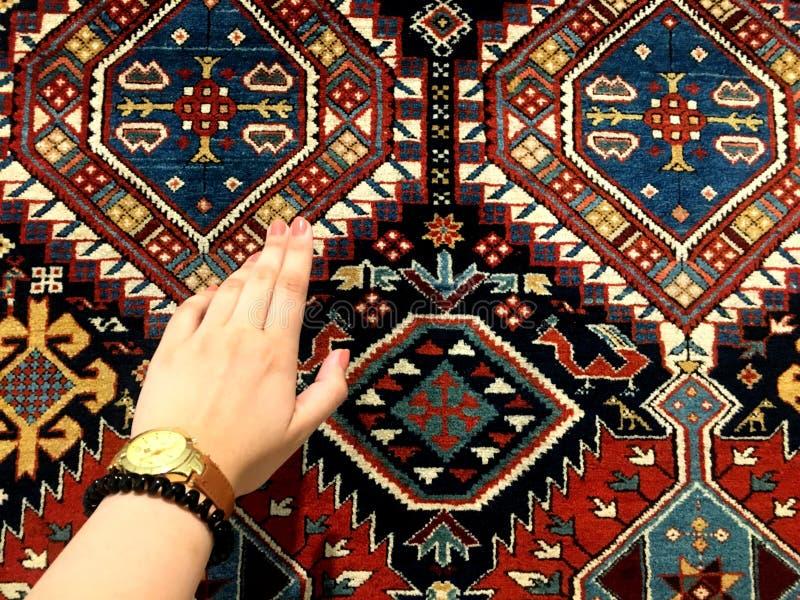妇女和东方地毯的柔和的手 独特的样式 图库摄影