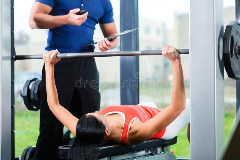 妇女和个人教练员在健身房 免版税库存图片
